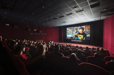 Přes hlavy diváků se ve zhasnutém kinosále díváme na plátno, na kterém běží film. Projekce diváky lehce osvětluje. /Over the heads of the spectators, we are looking at a screen on which a film flickers in a darkened theatre. The projected images softly illuminate the audience.