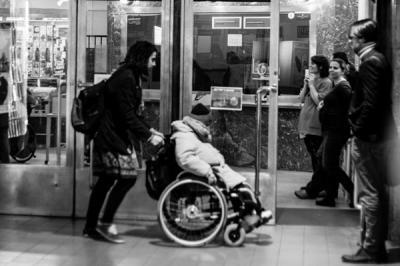 Do dveří k pokladně kina vstupuje člověk na vozíku, vozík vede žena. Dveře jsou prosklené. Po pravé straně stojí 3 lidé u stěny, vypadá to, jakoby dělali prostor vozíku./ A man in a wheelchair enters through the door to the cinema box office, a woman pushing the wheelchair. The door is made of glass. There are three people standing by the wall on the right; it looks like they are making room for the wheelchair.