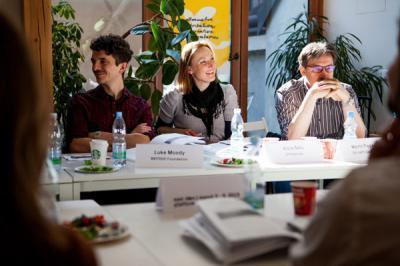 Tři lidé sedí v pozadí fotky za stolem, zleva tmovvlasý muž hledící doleva, uprostřed rozesmátá žena a vpravo muž opírající si obličej o ruce, za nimi jsou velké pokojové květiny a před nimi stůl s nečitelnými jmenovkami, lahvemi vody a nějakými papíry. / Three people sit at a table with photos in the background, a dark-haired man looking to the left, a smiling woman in the middle, and a man resting his face on his hand on the right. A large bouquet of flowers is behind them, and a table in front of them with illegible nametags, bottles of water, and some papers.