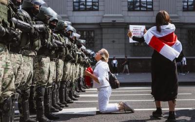 Protestující běloruska klečící žena, oblečená v bílém. Žena drží červenou látku a prosebně se dívá na vyrovnanou řadu vojáků stojící před ní./Protesting Belarusian kneeling woman dressed in white. A woman holds a red cloth and looks pleadingly at the balanced line of soldiers standing in front of her.