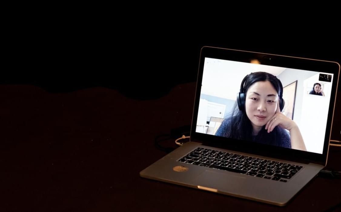 Notebook s jasnou obrazovkou je umístěn na pravé straně jinak tmavého obrazu. Na obrazovce notebooku vidíme hlavu ženy se sluchátky./A laptop with the bright screen is set in the right side of the otherwise dark image. On the screen of the laptop we see a woman