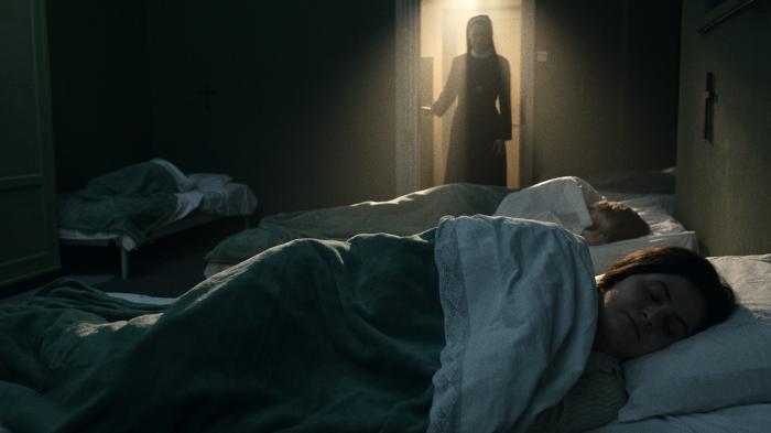 Do zhasnuté místnosti vchází jeptiška. Je nasvícená světlem zchodby. Vpřední části jsou dvě postele, na každé spí jedna žena. Na jednou postelí je křížek./A nun enters a dark room lit only by a light from the hallway. In front there are two beds, one woman sleeping in each. There is a cross over one bed.