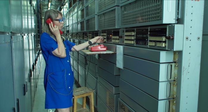 Žena vmodré zástěře stojí mezi vysokými regály. Vruce má červené sluchátko od vytáčecího telefonu, který stojí na poličce před ní.  Ztelefonu vede kabel, který žena zastrkuje do zdířky ve stěně, která slouží jako ústředna./A woman in a blue apron stands between high shelves. In her hand she holds the red handset of a rotary phone, which is standing on the shelf in front of her. A cable leads from the phone, which the woman plugs into the socket in the wall, which serves as a switchboard.