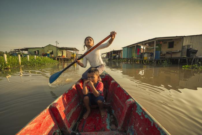 Uprostřed vodní plochy jedou malé děti na červené oprýskané loďce. Dívka pádluje na své pravé straně, pádlo zrovna vytáhla z vody. Dívá se do nebe, kluk je vpodřepu, kouše si prsty a jakoby se díval do kamery. Hladina vody je nahnědlá a klidná. Vpozadí jsou po obou stranách domy na kůlech a vlevo vyrůstá zvody zeleň. Fotka má výrazné barvy./Small children are riding on a peeling red boat in the middle of the water. A girl is paddling on her right side, she has just pulled the paddle out of the water. She looks at the sky, a boy is squatting, biting his fingers and appears to be looking at the camera. The surface of the water is brown and calm. In the background there are houses on stilts on both sides and plants are growing out of the water on the left. The photo has vibrant colours.