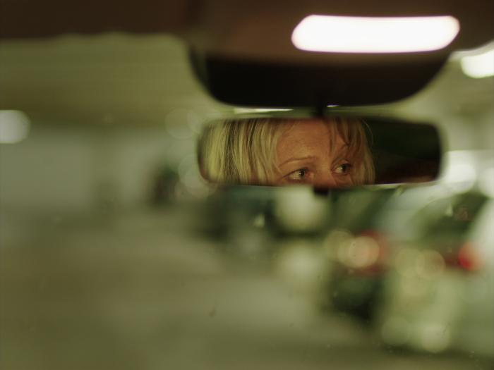 Ve zpětném zrcátku, které je vpravé části fotky, se odráží část tváře blonďaté ženy středního věku. Pozadí fotky je rozmazané, zbarvené do zelena spár odrazy světel jiných aut./The rear-view mirror, which is on the right side of the photo, reflects part of the face of a middle-aged blonde woman. The background of the photo is blurred, coloured green with a few reflections of the lights of other cars.