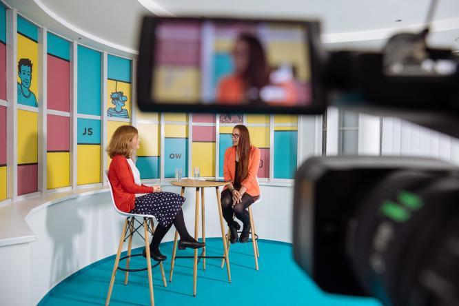 Dvě ženy sedí ve studiu ze kterého se online streamuje a spolu debatují/Two women, engaged in a debate, are sitting in an online streaming studio.